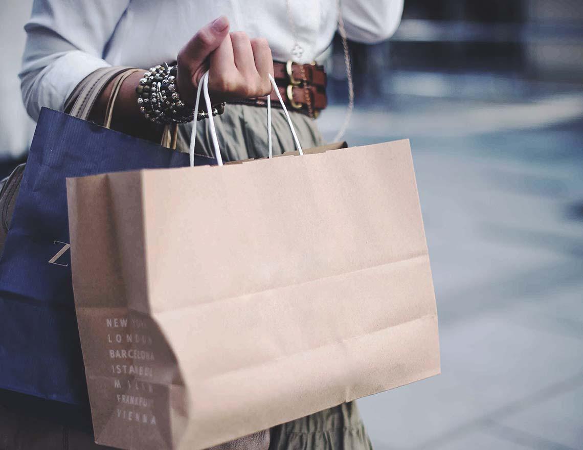 Eine Frau, welche 2 Einkaufstueten trägt